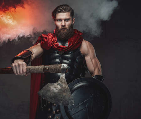 Brutal and armoured roman warrior with red cloak and outstretched arm which holding axe posing in dark room with smoke and spotlight.