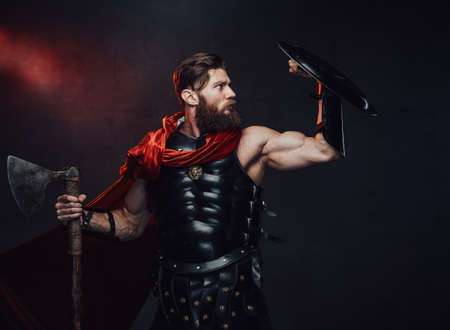 Handsome and muscular rome fighter with beard in dark armor and red cloak defends using his shield in dark background.