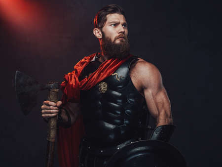 Warlike and armoured rome empire fighter with beard and muscular build posing holding shield and axe in dark room with spotlight.