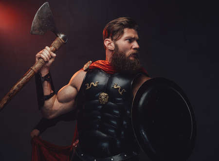 Bearded and muscular rome warrior in black armor and red cloak posing with axe and shield in dark studio background with spotlight. Banco de Imagens