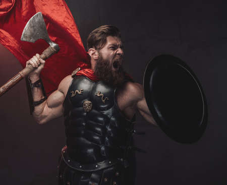 Warlike and muscular greek fighter with beard and red cloak posing screaming and holding axe and shield in dark background.