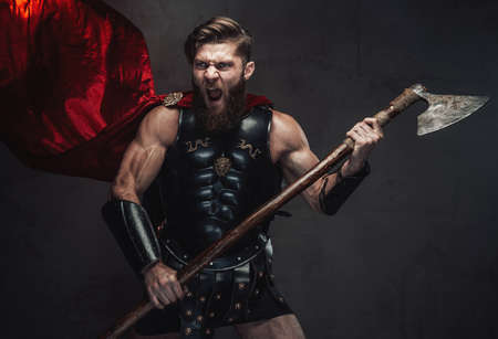 Aggressive combat rome warrior with beard in black armor screaming holding his two handed axe in dark background. Banco de Imagens