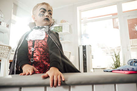 Male child in dark vampire costume posing in shiny and illumiated room at the halloween party. 写真素材