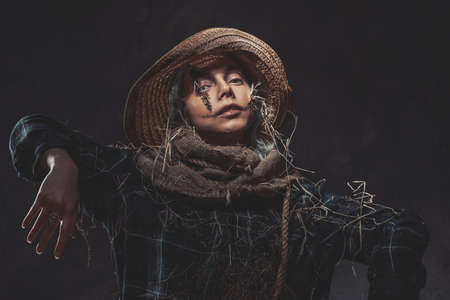 Woman with headwear in hey dressed like scarecrow with scars posing in dark background with hunging hands.