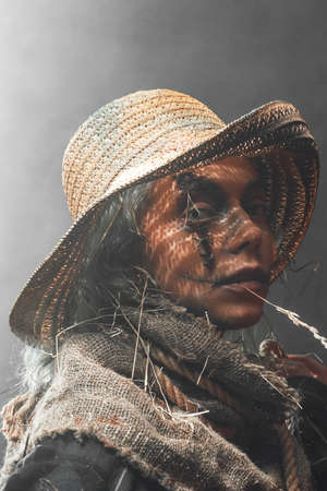 Atmospheric dark and illuminated background with smoke and scary and ripped woman in fashion of scarecrow with straw hat.