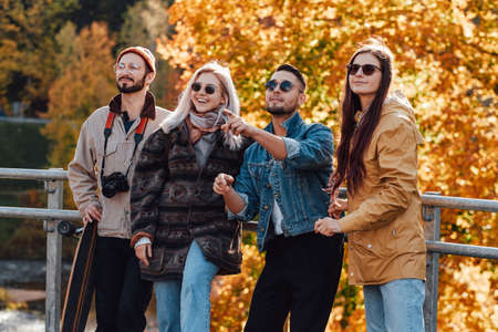 An autumn public park with yellow trees and four griends they are spending their holidays together and posing on bridge in daytime.