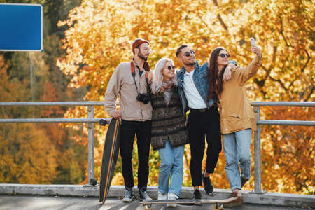 Group of two girls and two guys having a good time and spend their weekends together in autumn park in daytime. Reklamní fotografie
