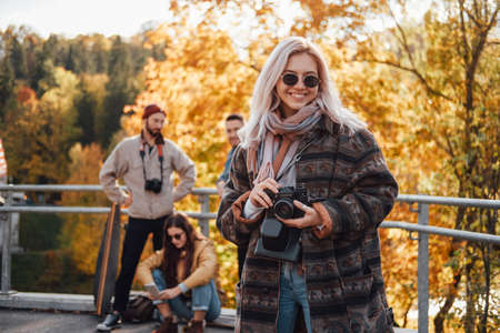 Happy beautiful blond posing with camera staying in foreground in background of autumn nature and her friends in daytime.