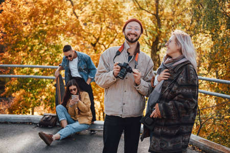 Joyful company of four friends having a good time and making photos in autumn public park in daytime.