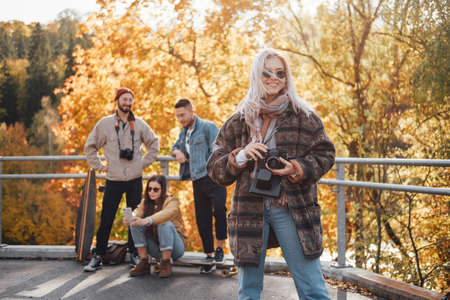 Pretty girl with blond hairs and camera posing in foreground in autumn landscape background and her friends in daytime.