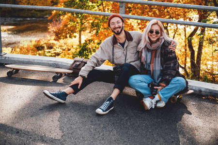 Bearded guy and blond girl relaxing embracing in nature sitting on skate in autumn landscape background.