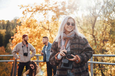 Fashionably dressed blond girl with sunglasses and camera having a good time with her friends in autumn public park.