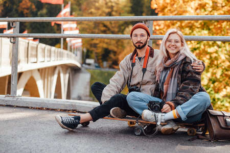 Couple in love of bearded photograph and blond girl in glasses posing sitting on skate in autumn landscape background.