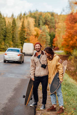 Embracing and joyful girl and guy stopping cars and going to rest after walking in lovely and golden autumn forest.