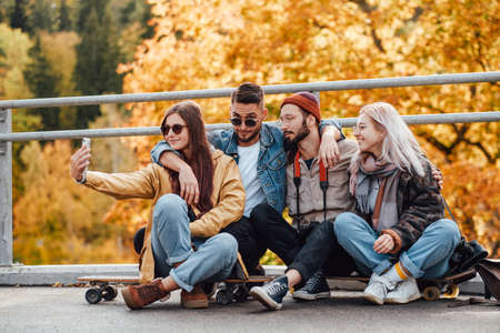 Joyful company of two girls and two boys dressed in autumn casual clothing photographing sitting on skates in public park. Reklamní fotografie
