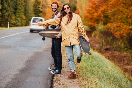 Two people pretty girl and bearded guy stopping car and holding their skates in background of lovely and relaxing autumn forest.