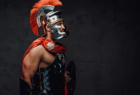 Armoured and serious imperial militray roman posing dressed with steel helmet and red mantle looking away in dark background.