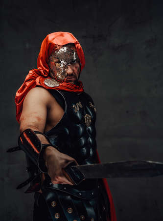 Imperial elite roman slayer with red hood and cloak with mask poses in dark background holding a sword. Archivio Fotografico