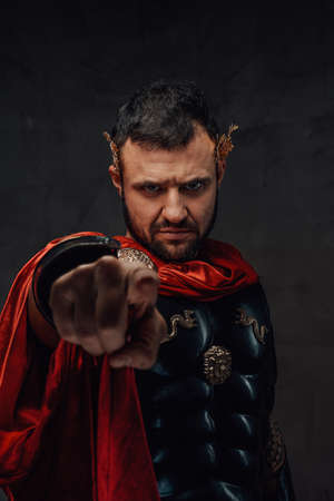 Serious and bearded roman emperor dressed in dark armour and red cloak points finger at camera in dark background. Archivio Fotografico