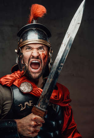 Mad roman soldier with blood on his face and dark armour screaming and attacking using his sword in dark background. Foto de archivo
