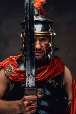 Warlike armoured roman warrior with red mantle posing holding his sword with serious face in dark background.