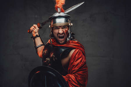 Screaming and assaulting mad roman warrior in armour and red mantle holding sword and shield in dark background. Archivio Fotografico
