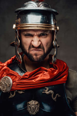 Mad and savage armoured roman soldier dressed in black armour and red mantle with helmet posing with angry face looking at camera.