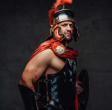 Armoured and serious imperial militray roman posing dressed with steel helmet and red mantle looking at camera in dark background. Archivio Fotografico
