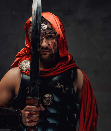 Elite killer from ancient rome with mask and red cloak poses with sword near his face in dark background.