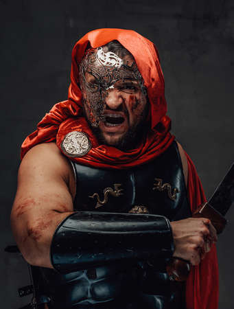 Savage roman slayer with blood on his face dressed in red cloak and weared with mask screams holding a sword in dark background.