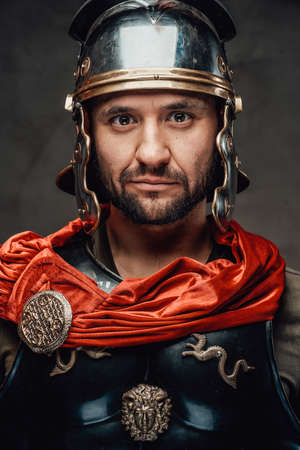 Bearded and serious roman fighter dressed in black armour and red mantle with helmet staring at camera in dark background.
