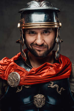 Smiley mature roman soldier in black armour with helmet and red mantle looking at camera in dark background.