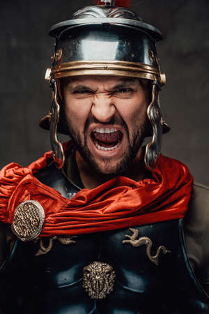 Savage bearded roman soldier dressed in black armour with helmet and red mantle screaming in dark background. Archivio Fotografico