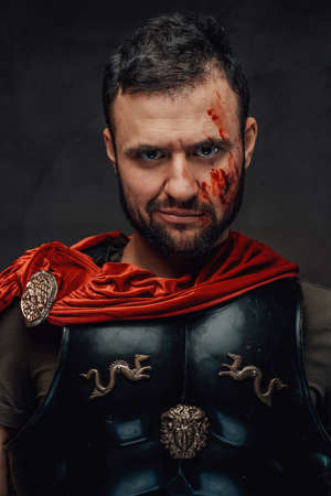 Serious and bearded roman emperor dressed in dark armour and red cloak