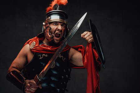 Attacking savage and brutal imperial soldier from rome in steel armour and red cloak holding sword and shield in dark background.