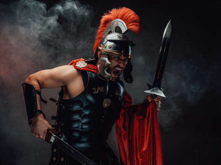 Brutal and savage roman soldier in dark armour with helmet and red cloak screams and assaults holding dual swords in smokey background.
