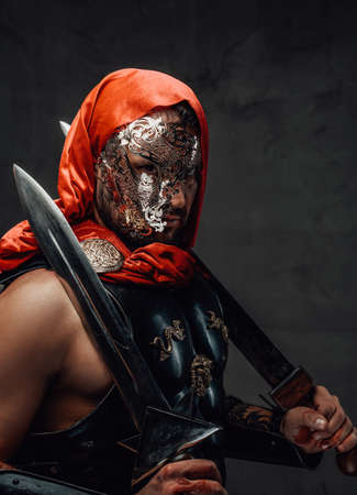 Imperial elite roman slayer with red hood and cloak with mask poses in dark background holding dual swords. Archivio Fotografico