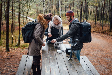 Shiny and lovely autumn forest and three students a guy and two girls they tuning quadcopter at table.