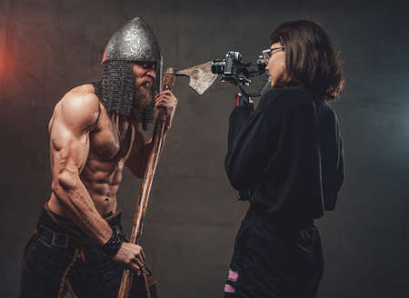Shirtless and muscular guy with axe and helmet in fashion of savage viking poses for camera while photographer shots him. Stock fotó