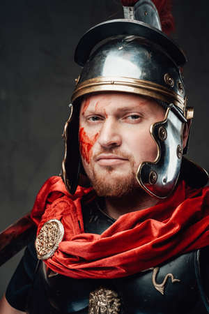 Headshot of bearded legionary he dressed in dark armour and helmet with red cape in dark background.