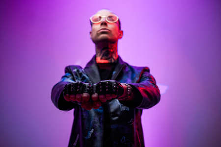 Serious and styled rocker in black leather jacket with glasses pulling his hands forward and poses in abstract background.