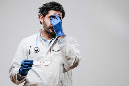 Tired doctor with stethoscope and rubber gloves dressed in labcoat took off his eyewears in white background.