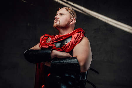 Bald roman elite and handsome human with wreath on his head and dark armour with red cape poses with crossed arms.