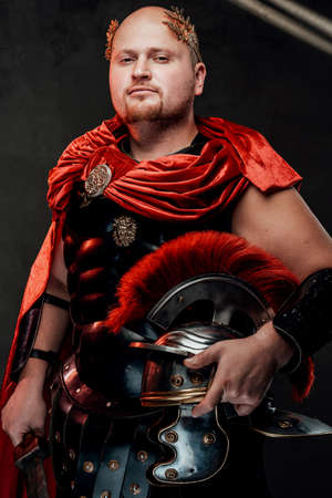 Handsome armoured roman warrior with bald head in black armour and red cape poses holding his gladius and helmet.