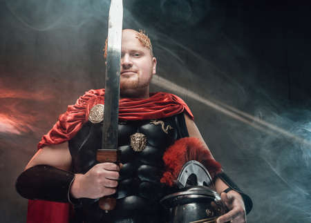 Handsome hairless roman soldier in dark armour and red cape poses holding helmet and sword in smokey background with lights.