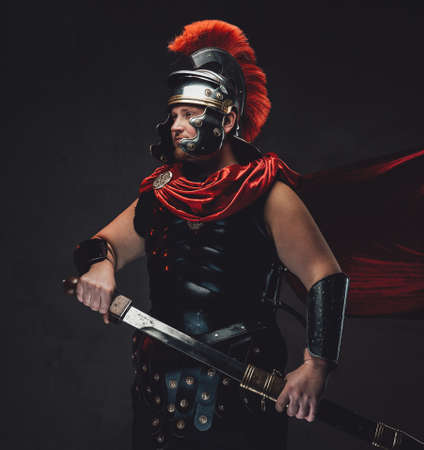 Handsome and warlike legionary in black armour with red cape and helmet poses with sheathed sword in dark background.