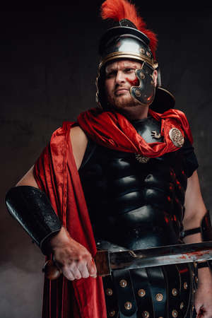 Strong and warlike legionary with blood on his face in black armour with red cape poses holding a sword and looking away.