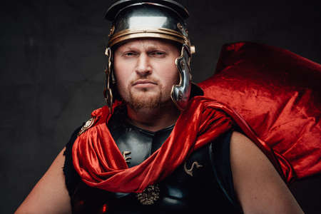 Headshot of warlike and serious legionary in helmet and black armour with red cape he poses in dark background looking at camera.