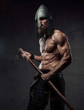 Furious and muscular nord warrior standing in dark background with torso and with his two handed axe.