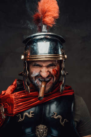 Mad imperial warrior from ancient rome with dark armour staring at camera with angry face smoking cigar in dark background.